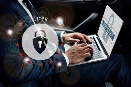 Photo pour Vue partielle d'un homme d'affaires américain africain utilisant un ordinateur portable en voiture avec illustration gdpr - image libre de droit