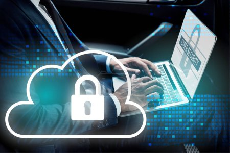 partial view of african american businessman using laptop in car with cyber security illustration