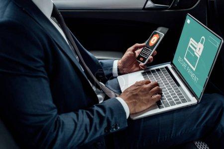Photo pour Vue recadrée d'un homme d'affaires afro-américain utilisant un ordinateur portable et un smartphone dans une voiture avec une illustration de cybersécurité - image libre de droit