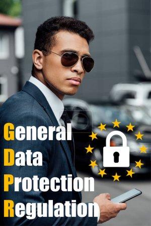 Photo pour Bel homme d'affaires africain américain en costume et lunettes de soleil avec smartphone et illustration gdpr - image libre de droit