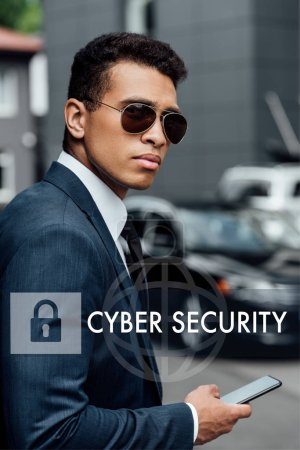 Photo for Handsome and confident african american businessman in suit and sunglasses using smartphone with internet security illustration - Royalty Free Image
