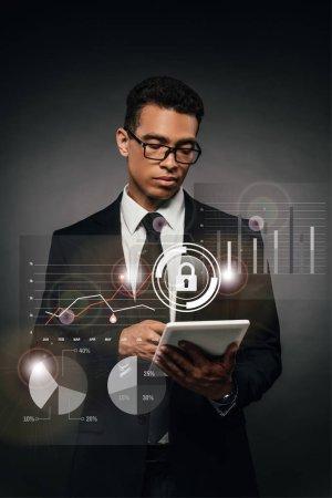 Photo pour Homme d'affaires américain d'origine africaine en lunettes utilisant une tablette numérique sur fond sombre avec une illustration de sécurité sur Internet - image libre de droit