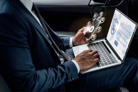 Photo pour Crochet vue d'un homme d'affaires américain africain utilisant un ordinateur portable et un smartphone en voiture avec illustration de la sécurité Internet - image libre de droit
