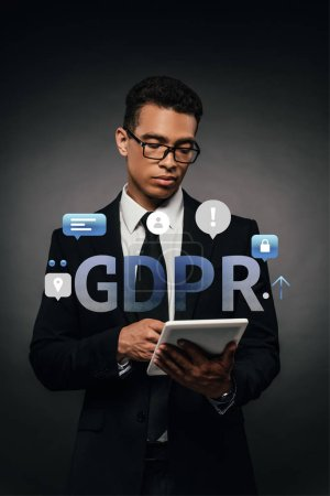 Photo for African american businessman in glasses using digital tablet on dark background with gdpr illustration - Royalty Free Image