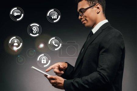 Photo pour Vue latérale d'un homme d'affaires américain d'origine africaine souriant utilisant une tablette numérique sur fond sombre illustrée d'icônes numériques - image libre de droit