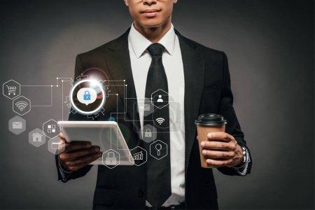 Photo pour Vue partielle de l'homme d'affaires afro-américain tenant café pour aller et tablette numérique sur fond sombre avec des icônes de sécurité Internet - image libre de droit