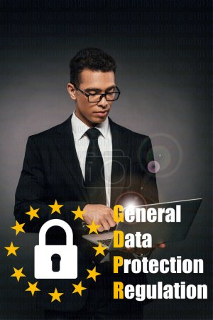 african american businessman using laptop on dark background with gdpr illustration