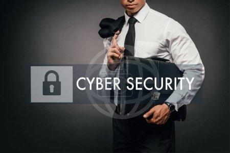 Photo pour Crochet vue d'un homme d'affaires africain américain tenant un blazer et un porte-documents en cuir sur fond sombre avec illustration de la cybersécurité - image libre de droit