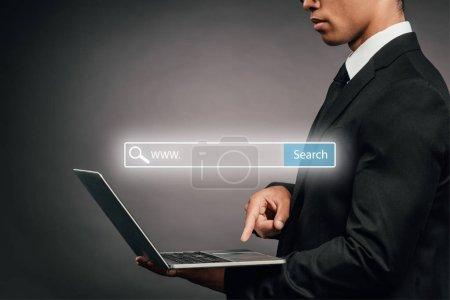 Photo pour Vue partielle d'un homme d'affaires américain africain utilisant un ordinateur portatif sur fond sombre avec illustration dans une barre de recherche - image libre de droit