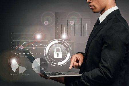Foto de Vista parcial del empresario africoamericano que utiliza laptop en un fondo oscuro con ilustración de seguridad en Internet. - Imagen libre de derechos