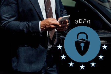 Photo pour Cropped view of african american business man in suit using smartphone at sunny day near car with gdpr illustration - image libre de droit