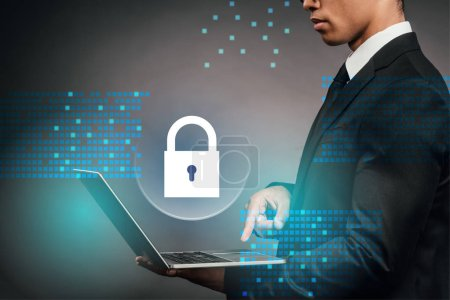 Photo for Partial view of african american businessman using laptop on dark background with internet security illustration - Royalty Free Image