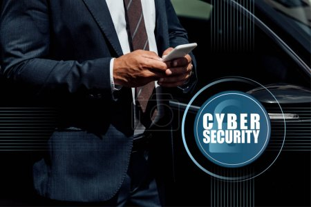 cropped view of african american businessman in suit using smartphone at sunny day near car with cyber security illustration