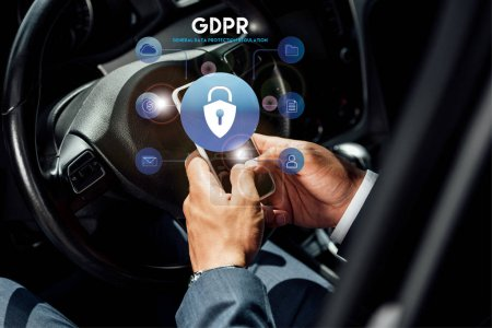 partial view of african american businessman in suit using smartphone with gdpr illustration in car at sunny day