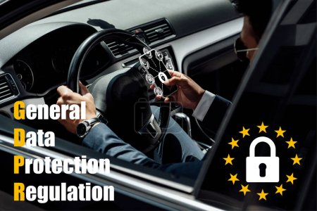 Photo for African american businessman in suit and sunglasses driving car and using smartphone with gdpr illustration - Royalty Free Image