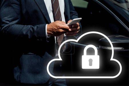 Foto de Vista panorámica del hombre de negocios africano-americano en traje usando smartphone en días soleados cerca del coche con ilustración de seguridad en Internet. - Imagen libre de derechos
