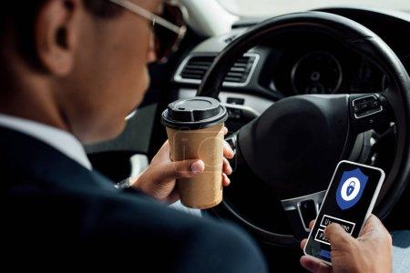 Photo pour Retour vue d'un homme d'affaires américain d'origine africaine utilisant un téléphone intelligent avec illustration d'accès sécurisé et buvant du café en voiture - image libre de droit