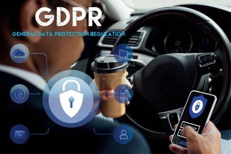 Foto de Vista trasera del empresario africoamericano que utiliza smartphone con ilustración de gdpr y café para beber en el coche. - Imagen libre de derechos