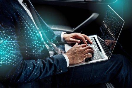 Photo pour Vue partielle d'un homme d'affaires américain africain utilisant un ordinateur portable avec illustration de la cybersécurité en voiture - image libre de droit