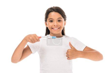 Photo pour Heureux enfant tenant brosse à dents et montrant pouce vers le haut isolé sur blanc - image libre de droit
