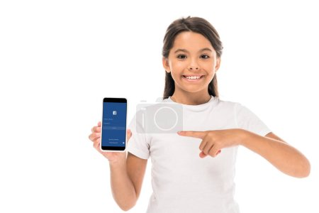 Photo for KYIV, UKRAINE - SEPTEMBER 3, 2019: happy kid pointing with finger at smartphone with facebook app on screen isolated on white - Royalty Free Image