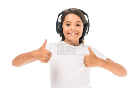 happy kid listening music in headphones and showing thumbs up isolated on white