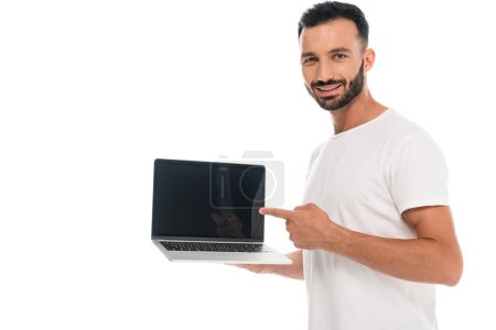 happy bearded man pointing with finger at laptop with blank screen isolated on white