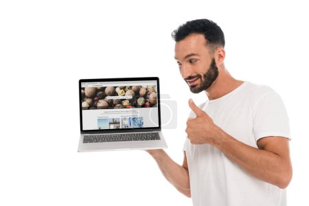 Photo pour Kyiv, Ukraine - 3 septembre 2019 : happy bearded man showing thumb up and looking at laptop with depositphotos website on screen isolated on white - image libre de droit