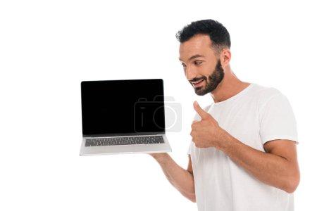 Photo pour Heureux homme barbu montrant pouce vers le haut et regardant ordinateur portable avec écran blanc isolé sur blanc - image libre de droit