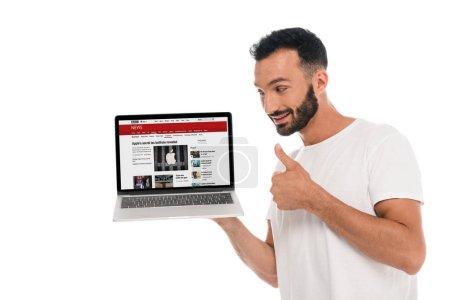KYIV, UKRAINE - 3 SEPTEMBRE 2019 : homme barbu heureux montrant pouce vers le haut et regardant un ordinateur portable avec le site de nouvelles bbc à l'écran isolé sur blanc