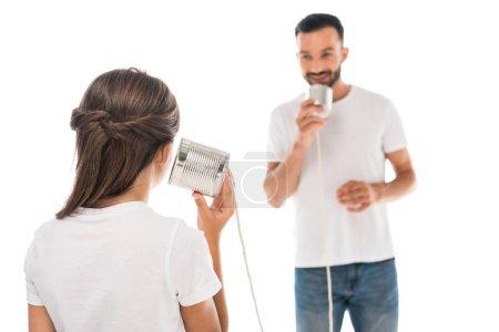 Photo pour Vue arrière du gamin jouant avec son père tout en tenant des boîtes de conserve isolées sur blanc - image libre de droit