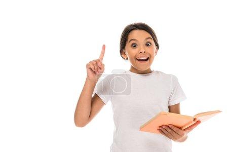 Photo pour Excité enfant tenant livre et pointant avec doigt isolé sur blanc - image libre de droit