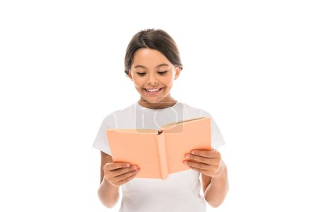 Photo pour Positive kid smiling while reading book isolated on white - image libre de droit