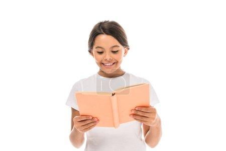 Photo pour Enfant positif souriant tout en lisant le livre isolé sur blanc - image libre de droit