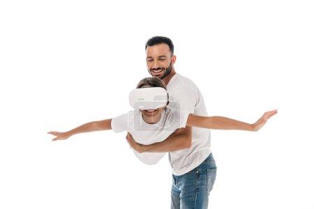 Foto de El padre feliz sosteniendo en brazos lindo niño en la realidad virtual auriculares aislados en blanco. - Imagen libre de derechos