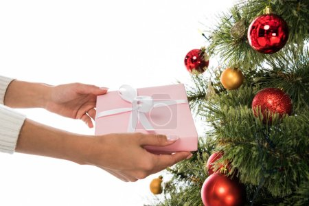 Photo pour Cropped view of woman holding present near christmas tree isolated on white - image libre de droit