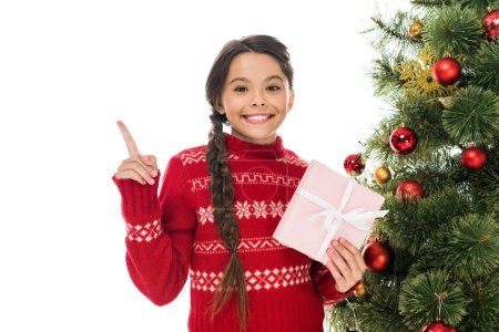 Photo pour Happy kid tenant rose présent et pointant du doigt près de l'arbre de Noël isolé sur blanc - image libre de droit