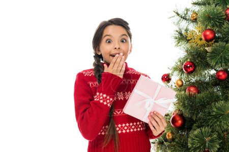 Photo pour Excited child covering face and holding pink present near christmas tree isolated on white - image libre de droit