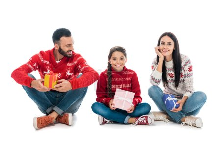Photo pour Happy family in sweaters holding gifts on white - image libre de droit