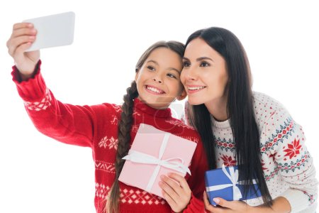 Photo pour Happy mother and daughter in sweaters taking selfie with present isolated on white - image libre de droit