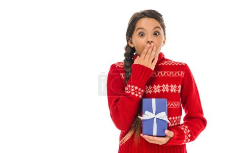 Photo for Surprised kid in sweater holding present and covering mouth isolated on white - Royalty Free Image