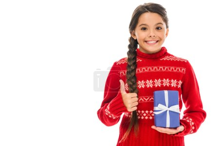 Photo for Happy kid in sweater holding present and showing thumb up isolated on white - Royalty Free Image