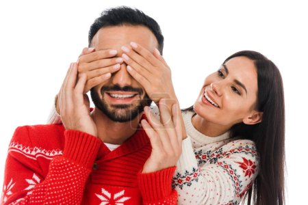 cheerful woman covering eyes of bearded man in sweater isolated on white