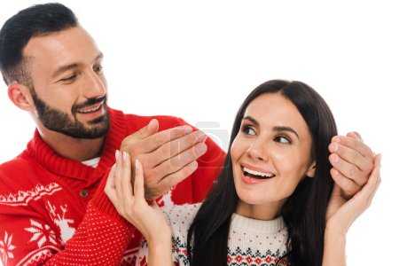 cheerful bearded man touching hands of attractive woman in sweater isolated on white