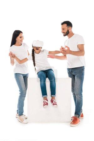 Photo pour Heureux parents tenant la main de fille en réalité virtuelle casque isolé sur blanc - image libre de droit