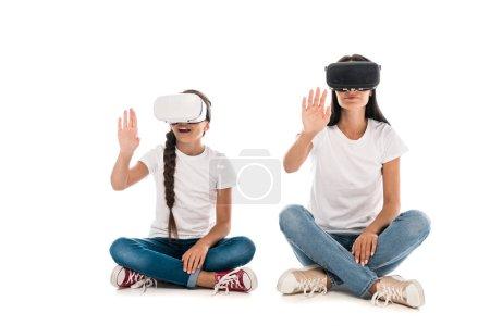 Photo pour Mère et fille à l'aide de casques de réalité virtuelle et geste isolé sur blanc - image libre de droit