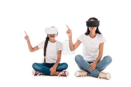 Foto de Madre e hija usando auriculares de realidad virtual y apuntando con dedos aislados sobre blanco. - Imagen libre de derechos