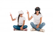 mother and daughter using virtual reality headsets and pointing with fingers isolated on white