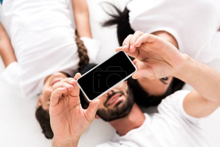 top view of happy bearded man holding smartphone with blank screen near wife and kid isolated on white