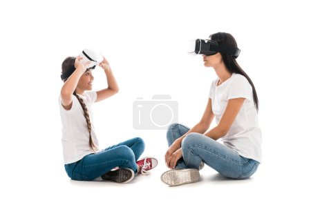 Photo for Cheerful kid looking at mother in virtual reality headset on white - Royalty Free Image